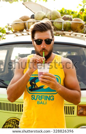 Outdoor portrait of hipster man,cool and stylish.Full length portrait of handsome young man holding ice juice on his hands and looking at camera,hippie young man,vintage image.Surfing men,freedom man - stock photo