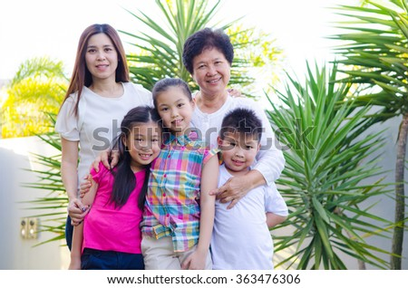 Outdoor portrait of lovely asian family - stock photo