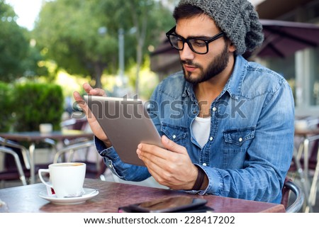 Outdoor portrait of modern young man with digital tablet in the street. - stock photo