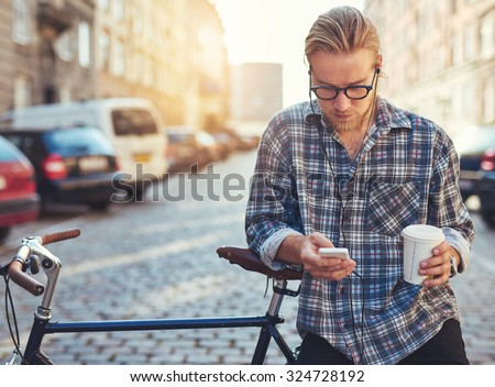Outdoor portrait of modern young man with mobile phone in the street, sitting on bike - stock photo