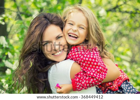 Outdoor portrait of mother and daughter - stock photo