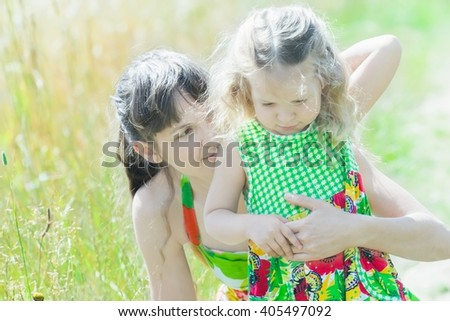Outdoor portrait of mother behind her little daughter are enjoying of being together - stock photo