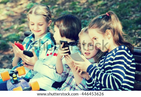Outdoor portrait of positive kids playing with phones - stock photo