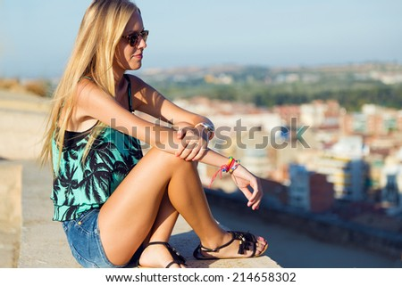 Outdoor portrait of pretty blonde girl sitting on the roof. - stock photo