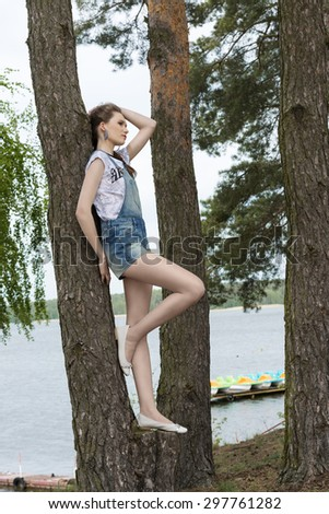 outdoor portrait of pretty girl with urban summer clothes posing in the nature near tree in fashion pose with lake on background - stock photo