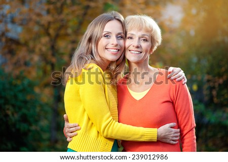 Outdoor portrait of  Pretty smiling Aged Mother and Adult Daughter Portrait Hugging in the autumn Park looking at camera - stock photo