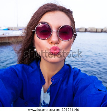 Outdoor portrait of pretty student girl taking a selfie.Beautiful urban woman taking picture of herself, selfie. Filtered image.Pretty hipster girl taking selfie and making duck face. Sending kisses  - stock photo