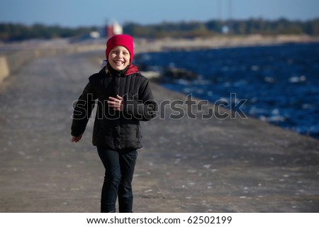 Outdoor portrait of running cheerful little girl - stock photo