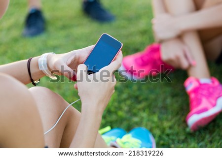 Outdoor portrait of running girls having fun in the park with mobile phone. - stock photo