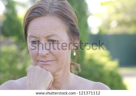 Outdoor portrait of sad and worried looking mature woman, isolated with blurred background - stock photo