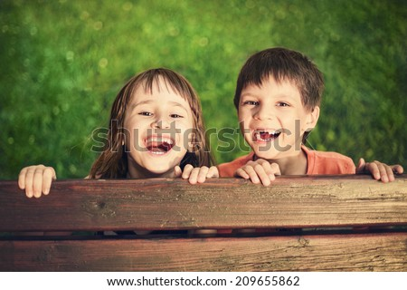 Outdoor portrait of smiling girl and boy who lost his milk teeth - stock photo