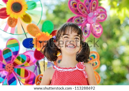Outdoor portrait of smiling little girl over colorful pinwheel background - stock photo