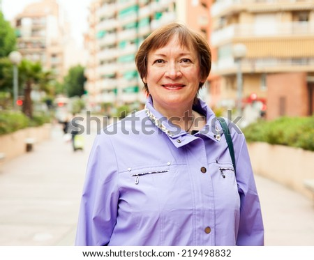 Outdoor portrait of smiling mature woman at european town street - stock photo