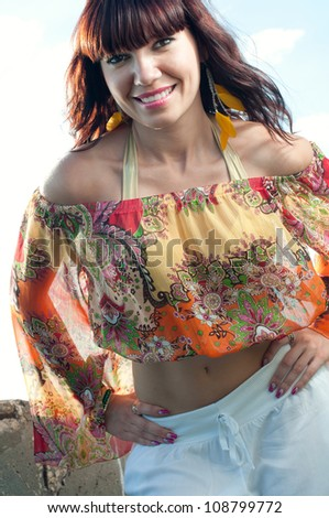 Outdoor portrait of smiling young woman enjoying summer evening - stock photo