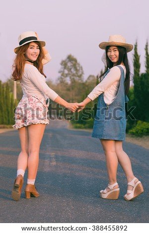 Outdoor portrait of teenage asian girls wearing a hat and hand in hand on the road, vintage tone - stock photo