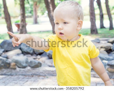 Outdoor portrait of tha cute baby pointing - stock photo