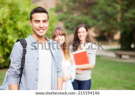Outdoor portrait of three smiling students in a park - stock photo