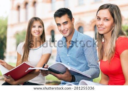 Outdoor portrait of three smiling students studying in a park - stock photo