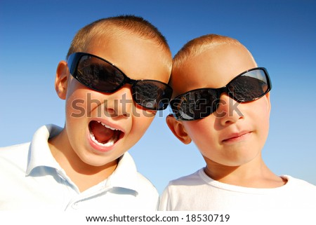 Outdoor portrait of two caucasian boys wearing black sunglasses in front of blue sky background - stock photo