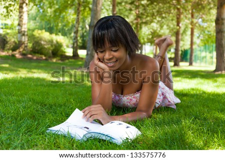 Outdoor portrait of young african american woman lying down on the grass reading a book - stock photo