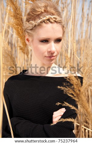 outdoor portrait of young attractive woman in the reed zone of park - stock photo