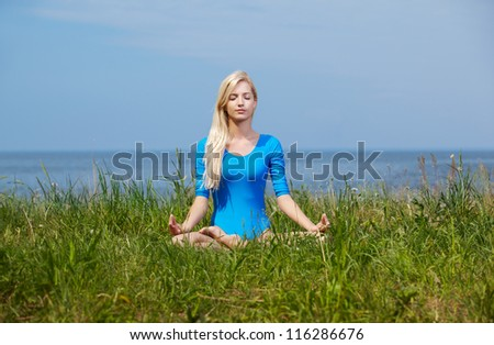 outdoor portrait of young beautiful blonde woman gymnast sitting in yoga lotus pose on green grass