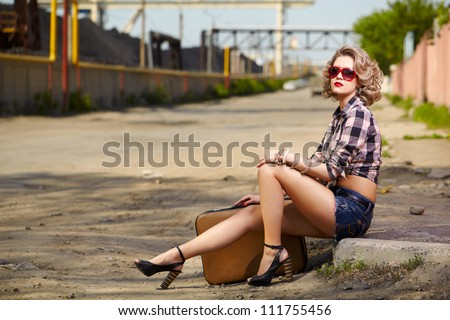 outdoor portrait of young beautiful blonde woman hitchhiker sitting on the roadside - stock photo