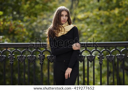 Outdoor portrait of young beautiful brunette woman with wavy long hair stares into camera posing against cast-iron fence with blurry forest background - stock photo