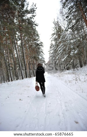 Outdoor portrait of young beautiful european style woman - walking through the winter forest wearing black coat and leather gloves - stock photo