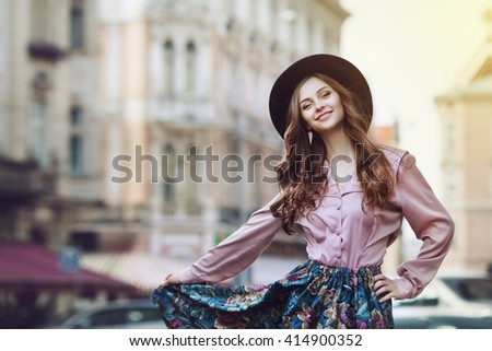 Outdoor portrait of young beautiful fashionable happy lady posing on a street of the old city. Model wearing stylish clothes. Girl looking at camera. Female fashion. City lifestyle. Copy space. Toned - stock photo