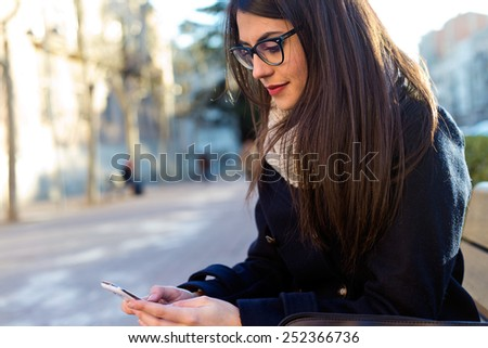 Outdoor portrait of young beautiful woman using her mobile phone. - stock photo