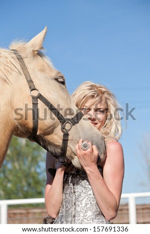 Outdoor portrait of young beautiful woman with horse - stock photo