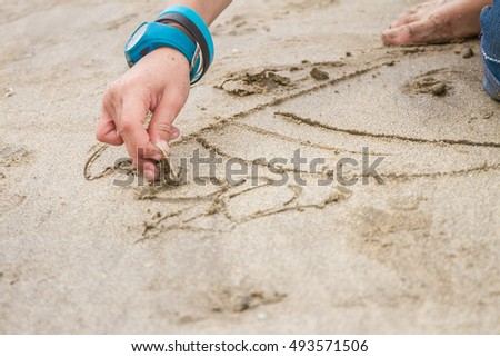 outdoor portrait of young boy drawing in sand on natural sea background