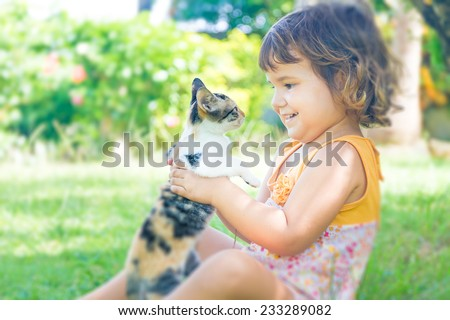 outdoor portrait of young child girl with small kitten, girl playing with cat on natural background - stock photo