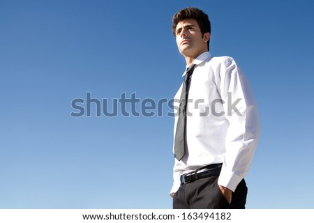 Outdoor portrait of young executive man looking at the horizon