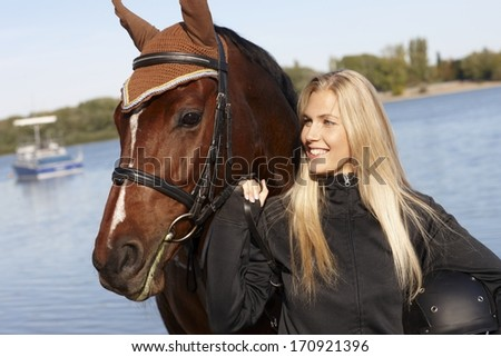 Outdoor portrait of young female rider and horse. - stock photo