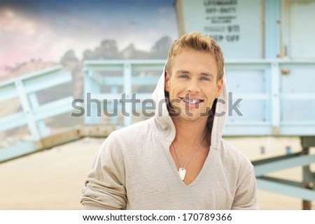 Outdoor portrait of young handsome man with big smile at the beach - stock photo