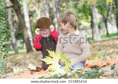 outdoor portrait of young happy children girl and boy on autumn forest background