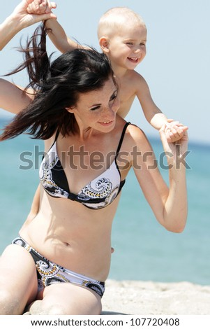 outdoor portrait of young happy mother and child on sea background