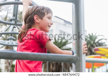 outdoor portrait of young happy smiling teen boy on sport/fitness playground