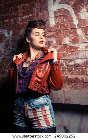 Outdoor portrait of young pretty girl. Beautiful woman posing in spring night with red jacket   - stock photo