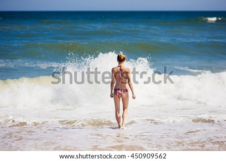 Outdoor portrait of young pretty woman posing near the ocean alone. Portrait of a girl going into the waves of a sea. Summertime, hot weather. - stock photo