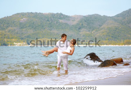 outdoor portrait of young romantic couple in white cotton clothes on beach of Phuket island, Thailand. guy is holding girl on hands - stock photo