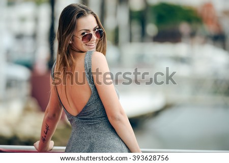 Outdoor portrait of young sexy tanned pretty woman standing on the pier near the sea marina. Back view of sensual girl in sunglasses - stock photo