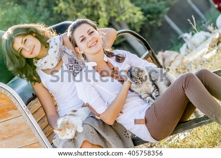 outdoor portrait of young two happy women with cat on natural background on farm - stock photo