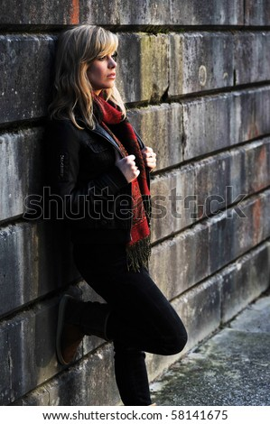 Outdoor Portrait Of Young Woman Leaning Against A Wall - stock photo