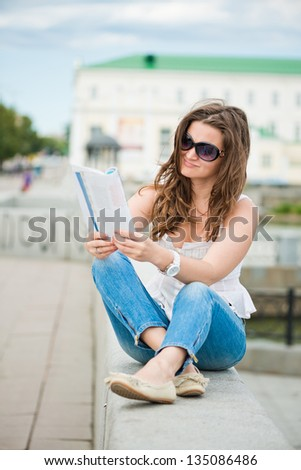 Outdoor portrait of young woman with fashion magazine - stock photo