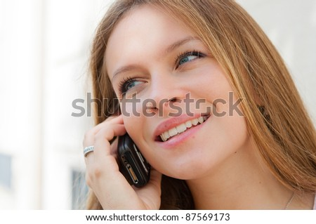 Outdoor portrait young woman talk on a cellular telephone