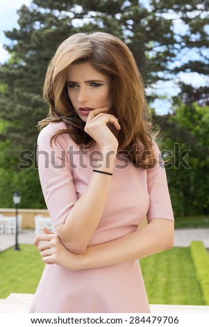 outdoor pretty portrait of a young girl charming expression, posing with garden in background ,  - stock photo