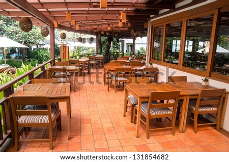 Outdoor restaurant interiour with wooden floor and furniture - stock photo